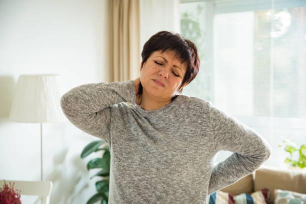 成熟的女人患有背痛在家裡 - 肌肉 個照片及圖片檔