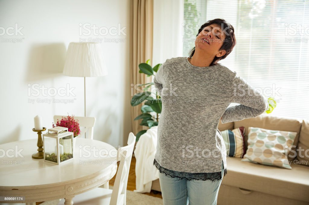 Mature woman suffering from backache at home stock photo