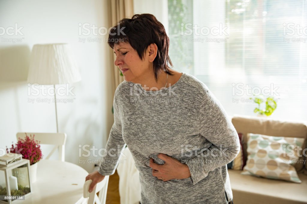 Mature woman suffering from stomach ache at home stock photo