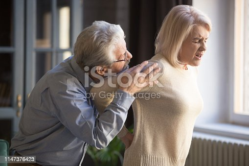 821012164istockphoto Mature woman suffering from sudden backache, old man supporting her 1147376423