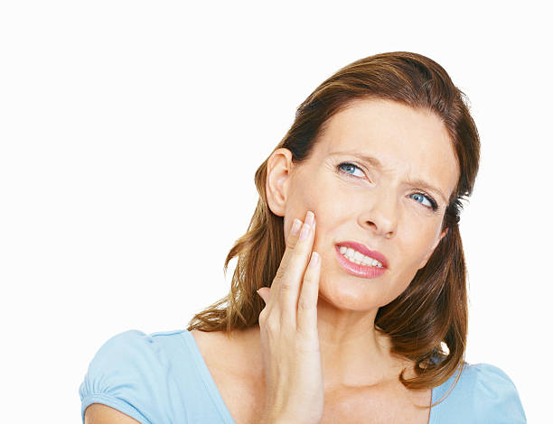 Mature woman suffering from toothache on white background stock photo