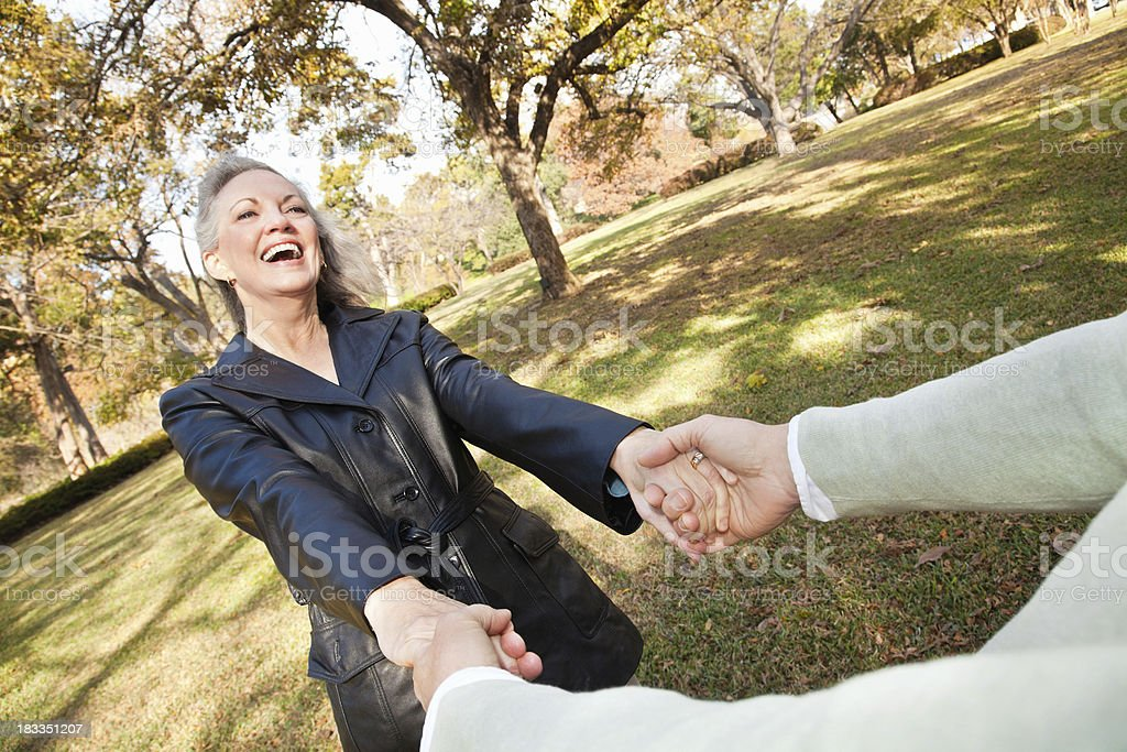 Mature Woman Swinging With Her Partner at a Park royalty-free stock photo