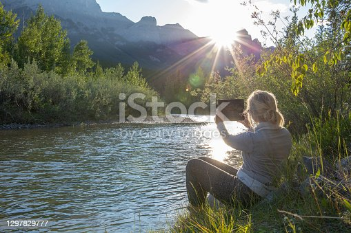 istock Mature woman takes photo with digital tablet on riverbank 1297829777