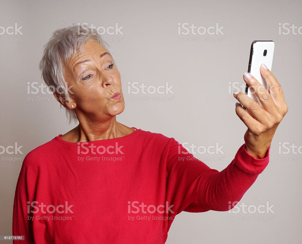 mature woman taking a smartphone selfie with duck face – Foto