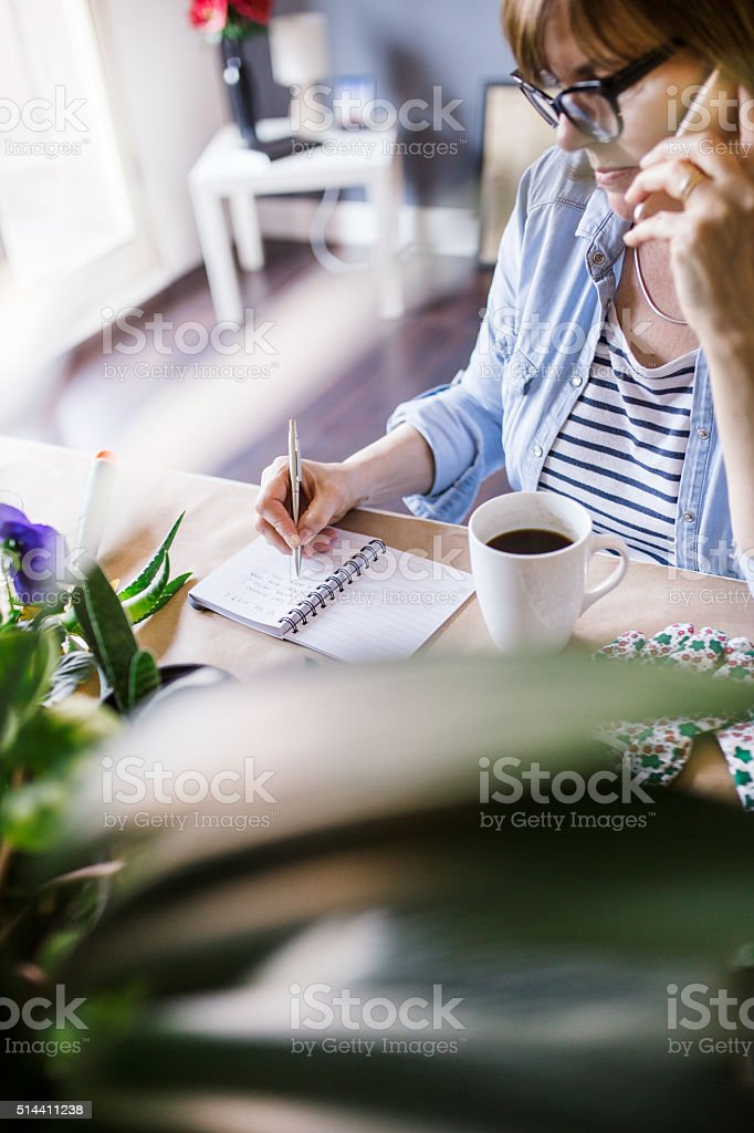 Mature woman taking notes in her home office stock photo
