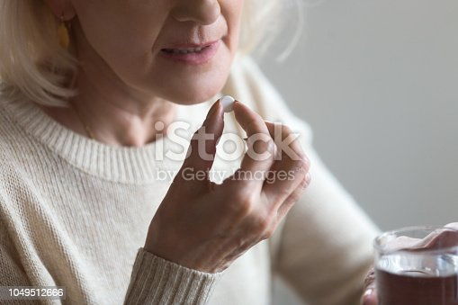 istock Mature woman taking pill holding glass of water, closeup view 1049512666