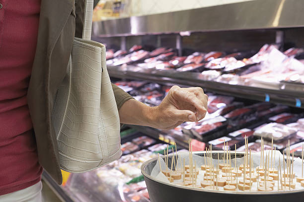 Mature woman taking sample in supermarket, mid section, close-up stock photo