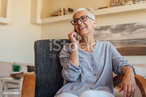 Senior woman having a mobile phone conversation while resting at home