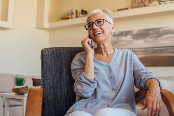 mature woman talking on mobile phone - person using phone stock photos and pictures