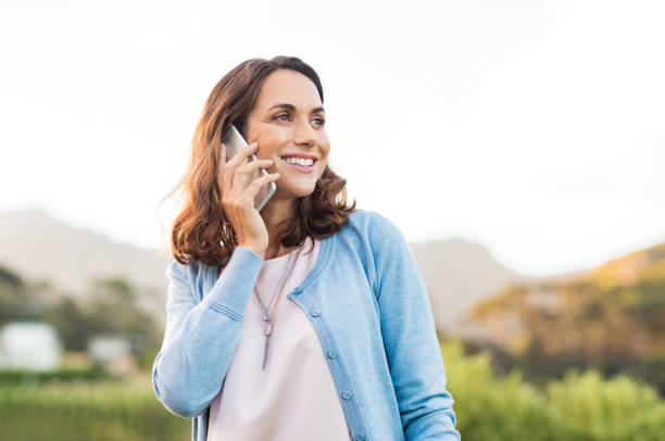mature woman talking on phone - older woman phone stock photos and pictures