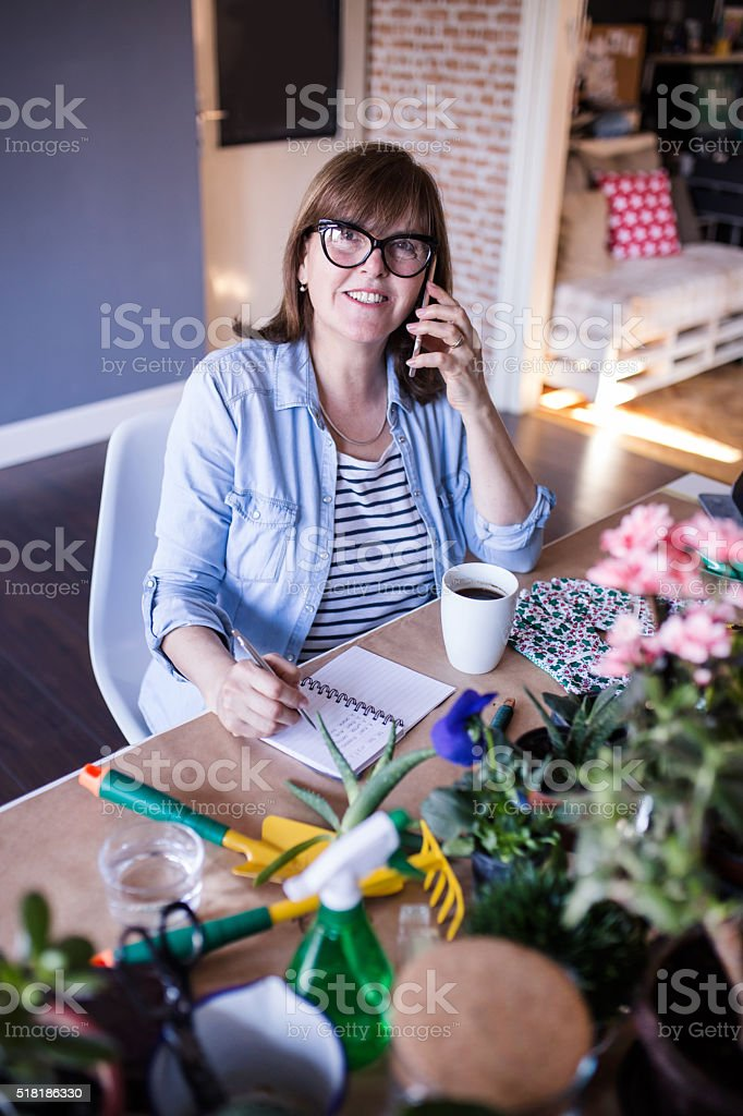 Mature woman talking on the phone in home office stock photo