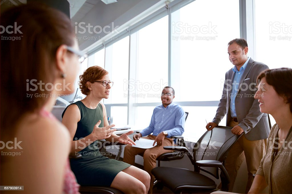 Mature woman talking with business colleagues in office stock photo