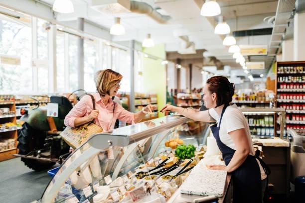 Reife Frau Verkostung Käse Probe bei Delicatessen – Foto