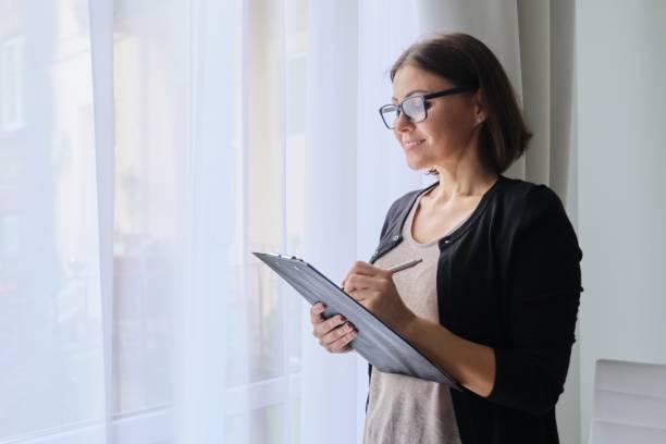 Olgun kadın öğretmen notlar alıyor, ofiste pencerenin yanında duruyor stok fotoğrafı