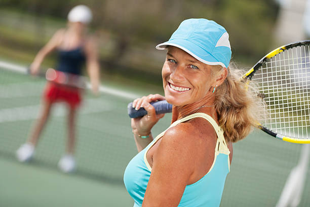 Mature woman tennis portrait Close-up of mature woman tennis player ready to play looking at camera. opponent in background. individual event stock pictures, royalty-free photos & images
