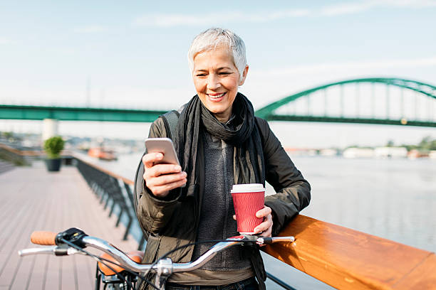 mature woman texting on her smart phone and drinking coffee - older woman phone stock photos and pictures