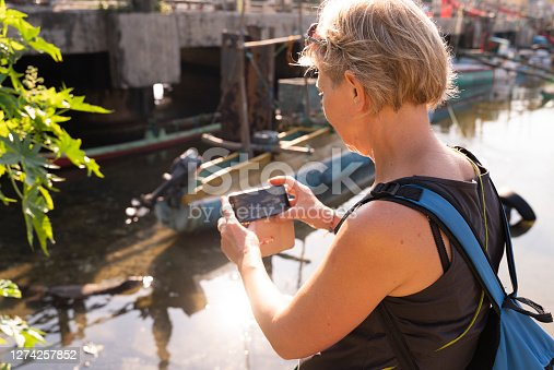 Mature woman, traveler, taking a photo of the giant water monitor in a stream in Sri Lanka.