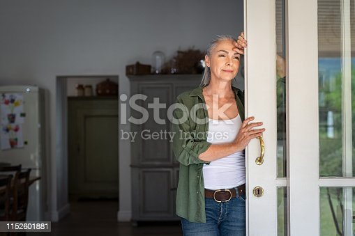 istock Mature woman thinking at home entrance 1152601881