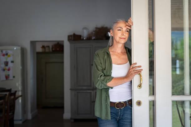 dojrzała kobieta myśląca przy wejściu do domu - nadzieja zdjęcia i obrazy z banku zdjęć