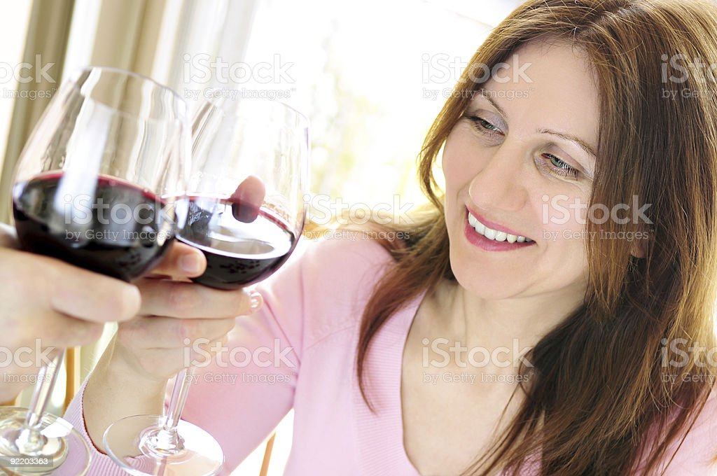 Mature woman toasting with red wine royalty-free stock photo