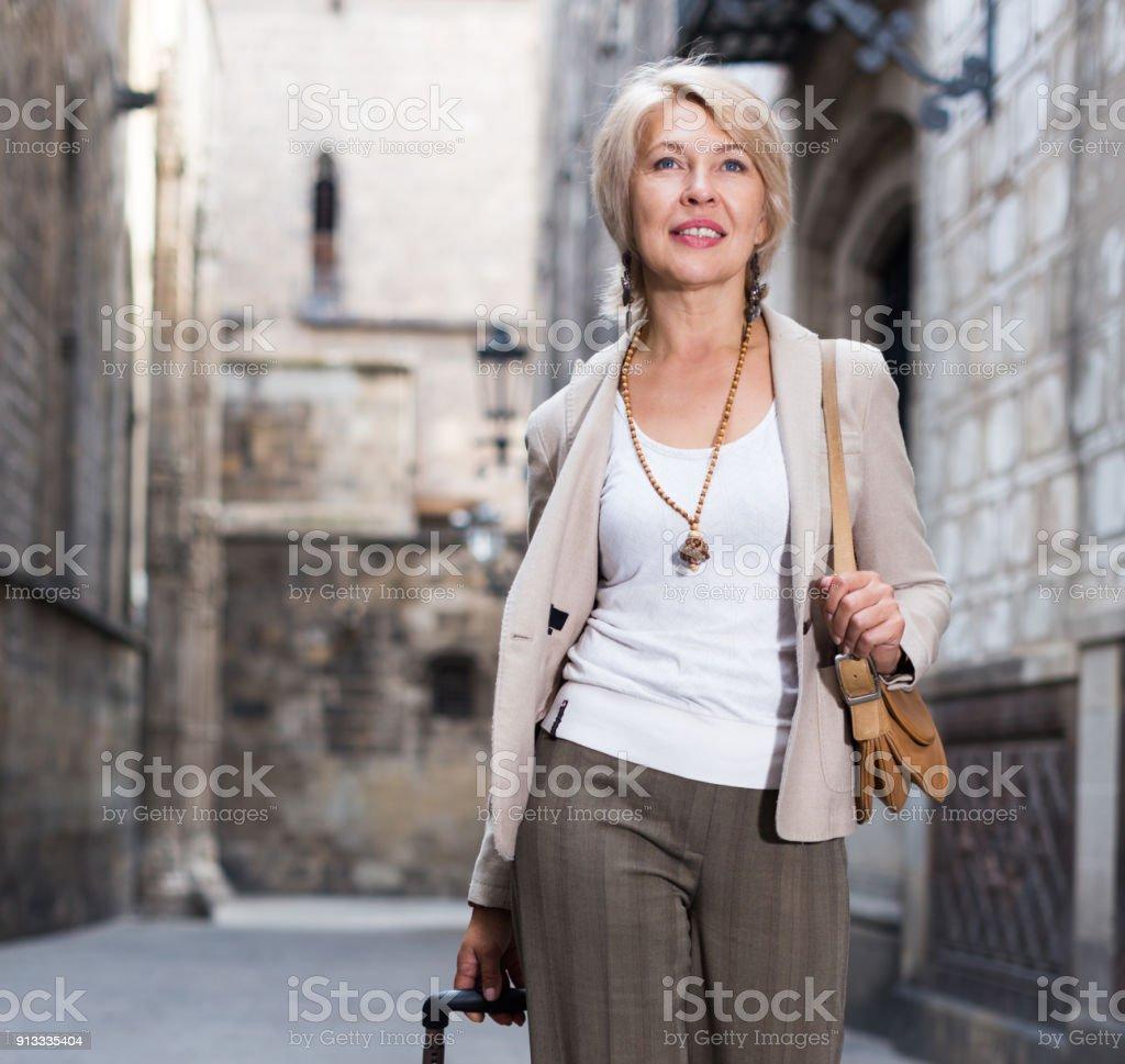Turista de mulher madura está caminhando com vestido clássico - foto de acervo