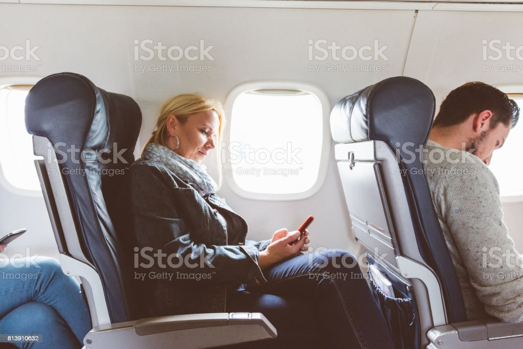 Mature woman traveling by airplane with mobile phone stock photo