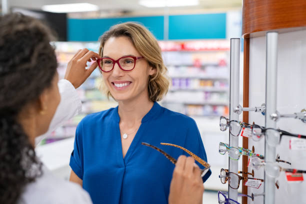 Mature woman trying new eyeglasses with optician stock photo