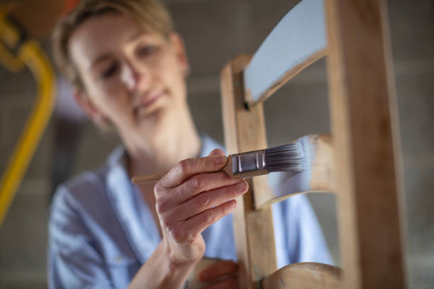 Reife Frau Upcycling Möbel In Workshop zu Hause Malerei Holzstuhl – Foto