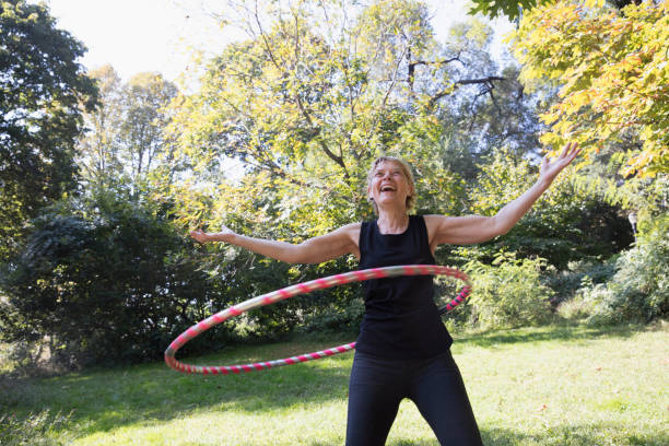 Mature woman using a plastic hoop at the park
