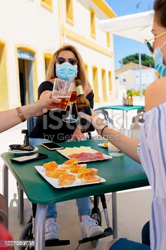 Mature woman using a wheelchair and a surgical mask doing a toast with other people at an outdoor bar terrace on an out of focus background. New lifestyle and disability concept.