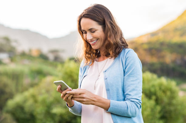 mature woman using cellphone - older woman phone stock photos and pictures