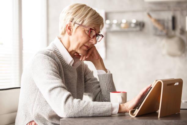 Reife Frau mit digitalen Tablet zu Hause – Foto