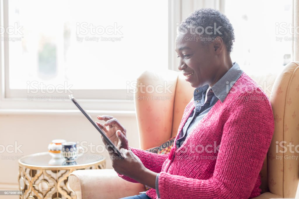 Mature woman using digital tablet stock photo