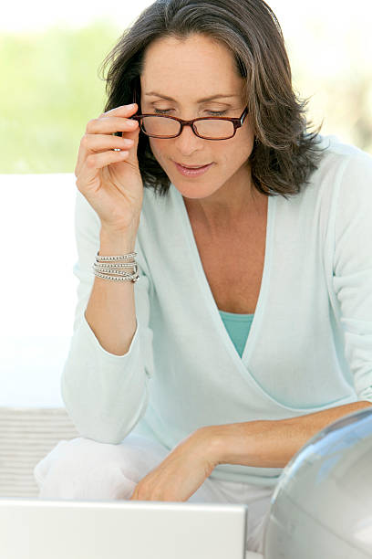 Mature woman using glasses stock photo