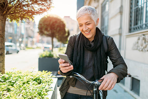 mature woman using her smart phone on bicycle. - older woman phone stock photos and pictures