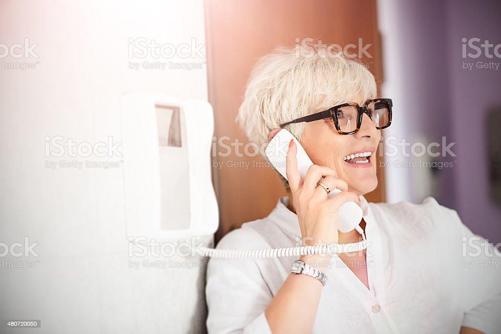 Mature woman using interphone home stock photo