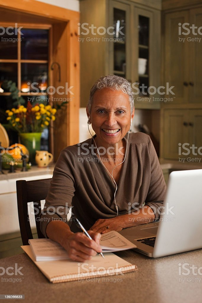 Mature woman using laptop and wearing ear phones, portrait royalty-free stock photo