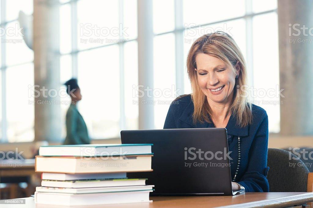 Mature woman using laptop, studying in modern library bildbanksfoto