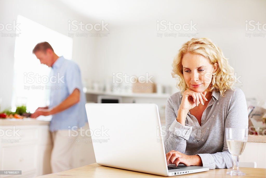 Mature woman using laptop while man cooking in kitchen royalty-free stock photo