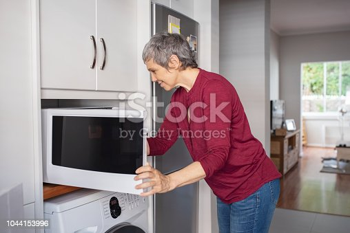 istock Mature woman using microwave oven 1044153996