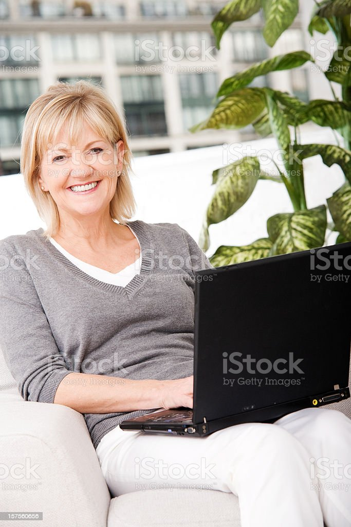 Mature Woman Using Notebook Computer at Home stock photo
