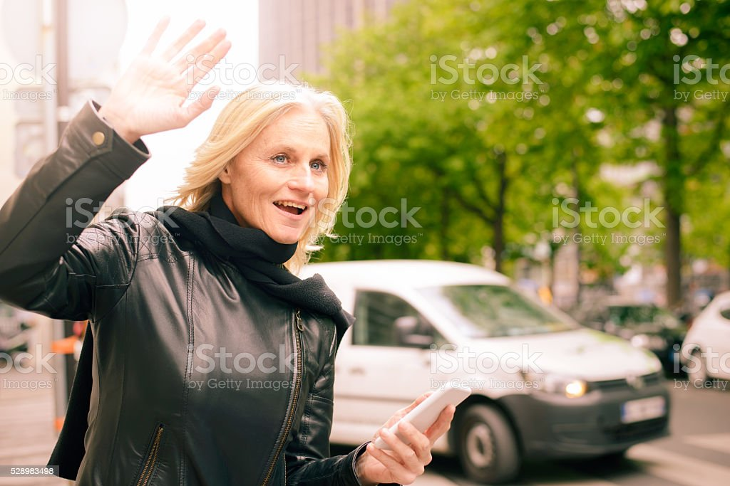 Mature Woman Using Smartphone App for Taxi Service stock photo