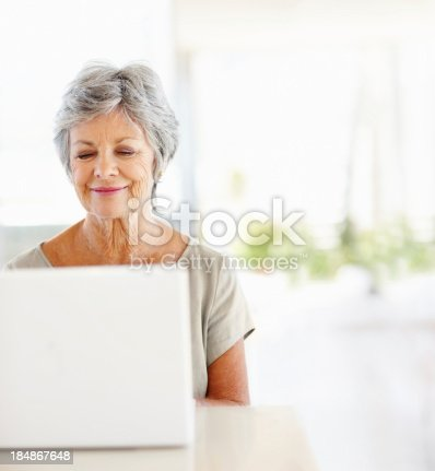 Happy mature woman using a laptop at home