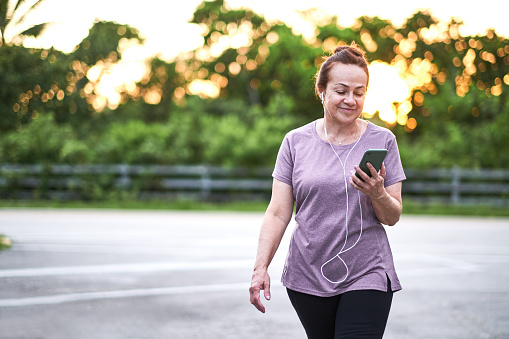 Beautiful mature Brazilian woman walking outside at park using mobile device at sunset