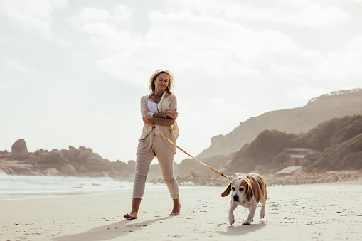 Mature woman walking her dog on the beach