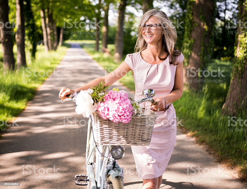 Mature woman walking through a park with her classic bicycle stock photo