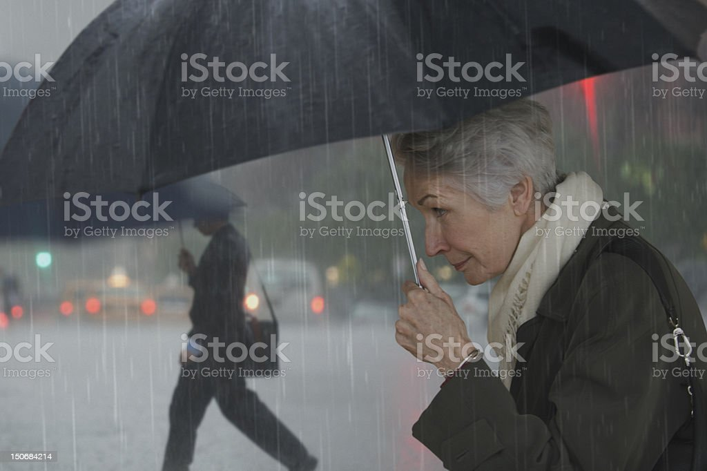 Mature woman walking with umbrella royalty-free stock photo