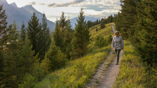 Mature woman walks down trail in the morning stock photo