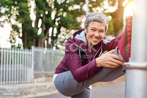 istock Mature woman warming up before jogging 1044161320