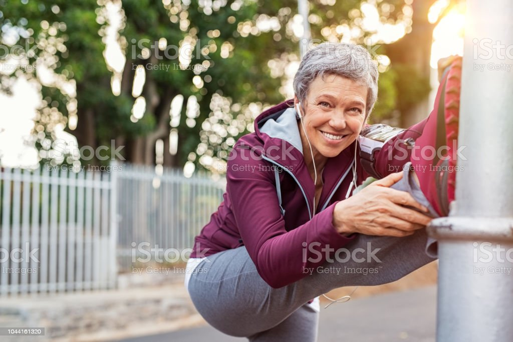 Femme d'âge mûr réchauffer avant de faire du jogging - Photo